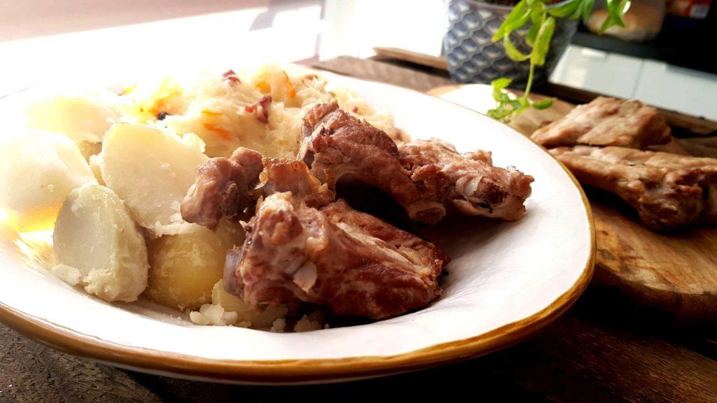 Braised pork ribs alongside sauerkraut and some mashed potatoes